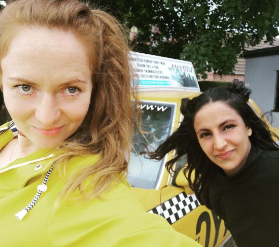 One woman wearing a yellow waterproof jacket and one woman wearing a black polo neck shirt in front of a yellow New York style taxi