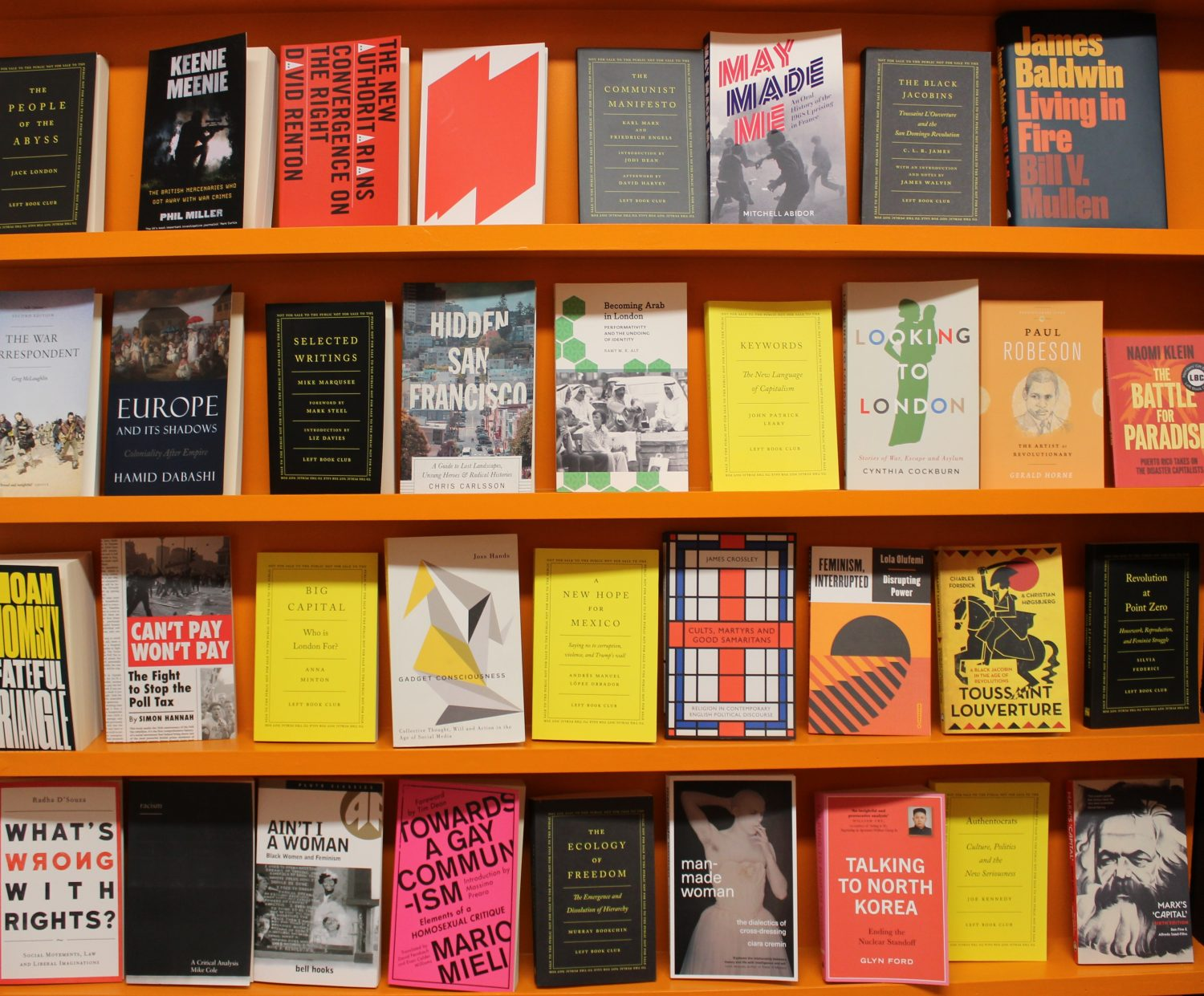 A landscape image of a bookcase stocked top to bottom with books. The bookcase is a bright orange colour, with the books having a range of different colour covers some yellow, pink and black.
