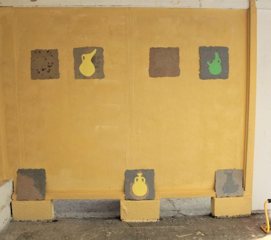 Wall painted yellow and white with a series of paintings on recycled card canvases mounted and placed on breezeblocks. The paintings are silhouettes of various jugs and pots, with some card canvases unpainted.
