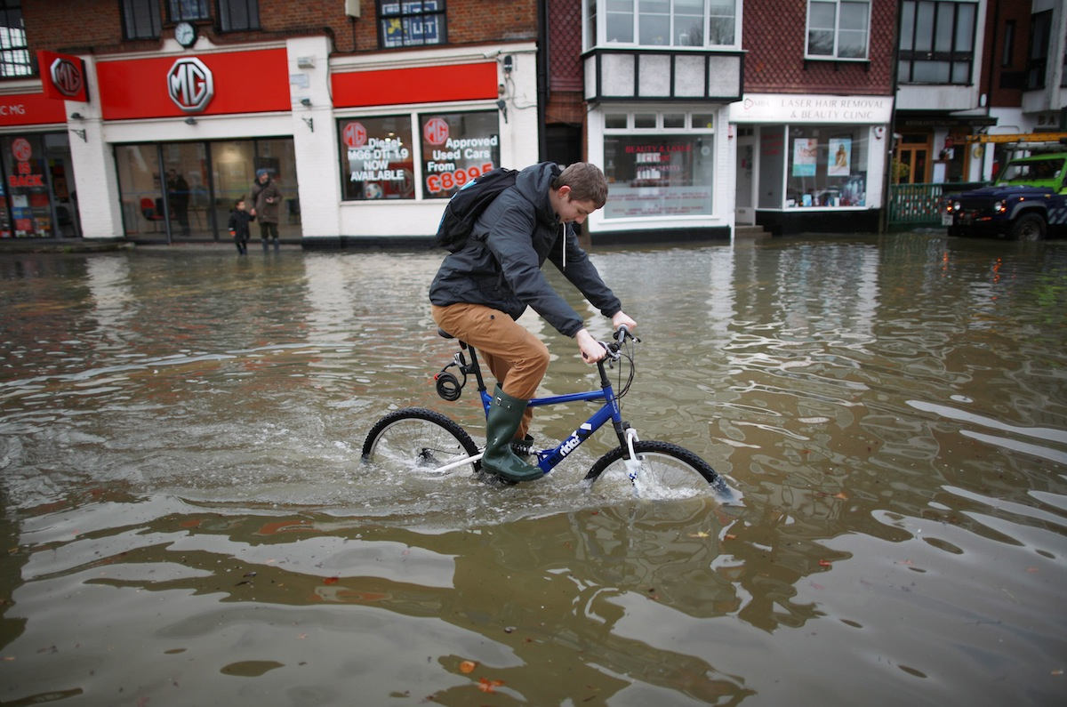 DATCHET, ENGLAND - FEBRUARY 10:  A youth cycles through flood water after the river Thames burst it's banks on February 10, 2014 in Datchet, England. The Environment Agency has issued severe flood warnings for a number of areas on the river Thames west of London.  (Photo by Peter Macdiarmid/Getty Images)